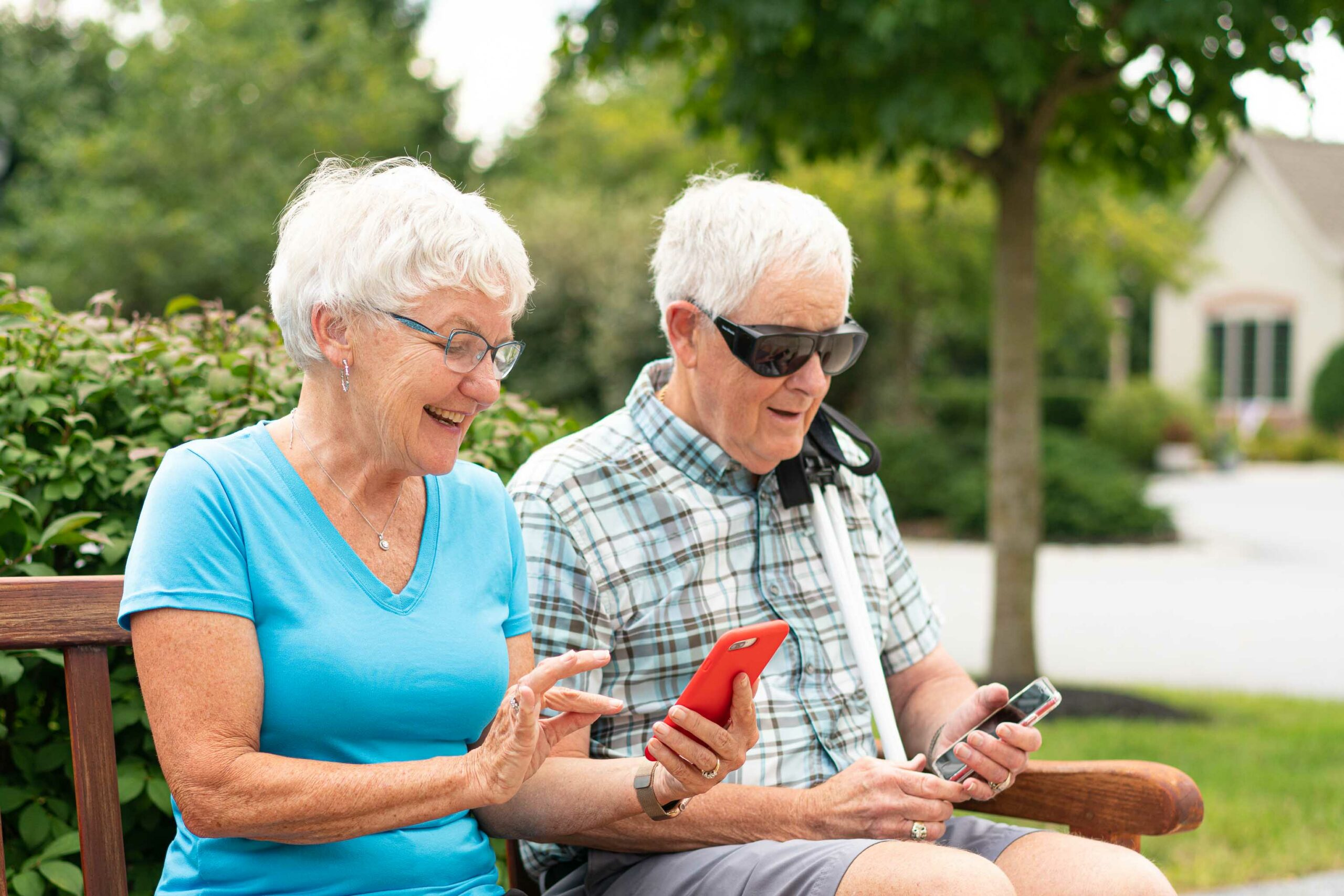 A man and woman sit on a bench together. The woman, with silver hair and blue shirt, is looking at her cell phone. The man, with silver hair and plaid shirt, wearing sun shields, is also looking at a cell phone.