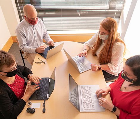 Four coworkers around a conference table while typing on their laptops.