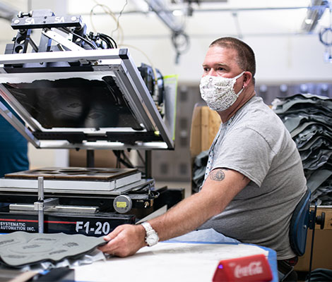 A man in a grey shirt and face mask operates a printing machine.