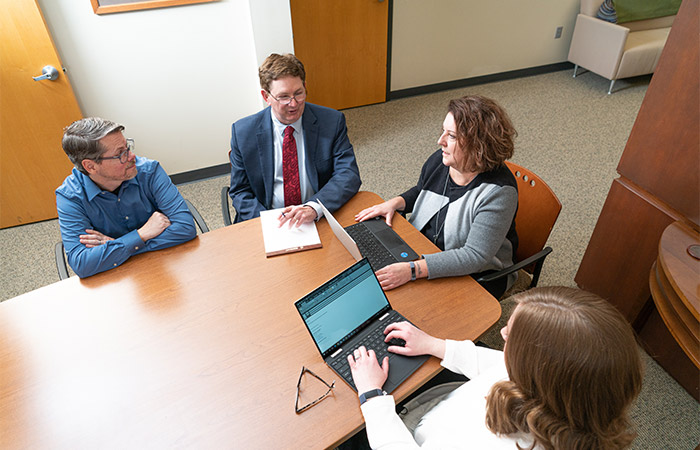 Two men and two women surround a conference table while typing on computers and writing on a note pad.