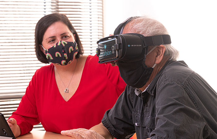 A middle aged woman sits beside a middle aged man. He is wearing Iris VIsion smart glasses and the woman helps to adjust them on his face