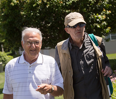 An older man volunteers to help provide sighted guide to a middle aged male client.