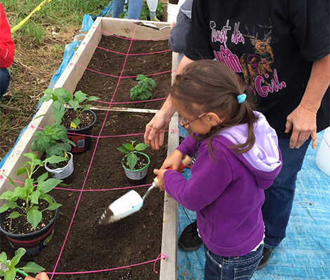 A little girl holds a small garden shovel to dirt in a raised garden bed, while a middle aged female volunteer looks on.
