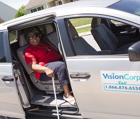 An older woman in a bright red shirt sits in the back seat of a VisionCorps van, waiting for the volunteer driver to transport her.