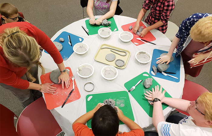 A table with children around it working with clay is photographed from overhead.