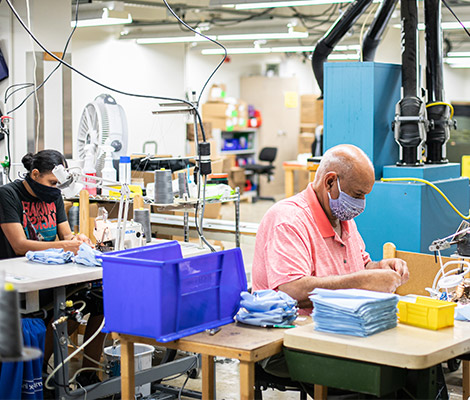 Two employees work diligently on sewing products.